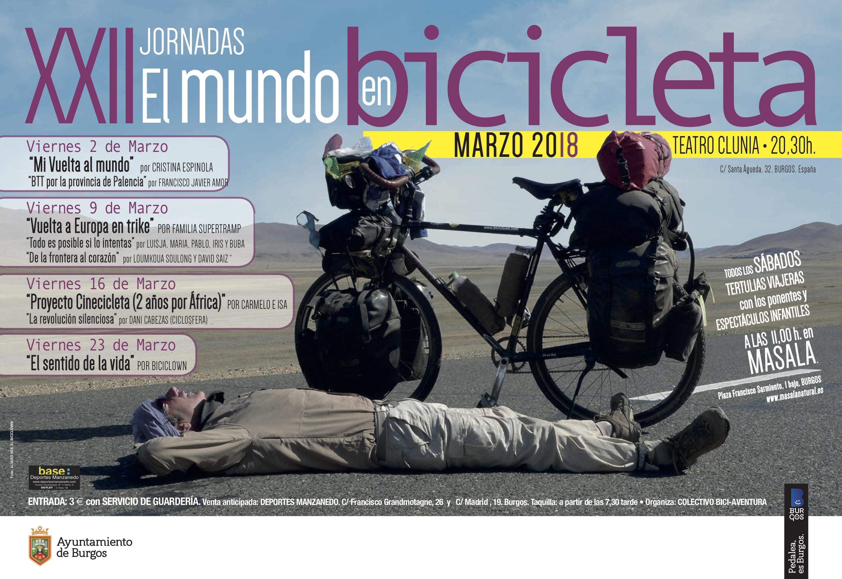 Cicloviajero descansando tumbado en una carretera a los pies de su bici