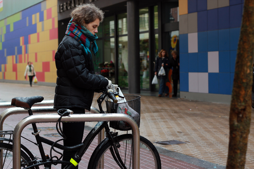 ciclista colocando bolsas de compra en cesta delantera de la bici
