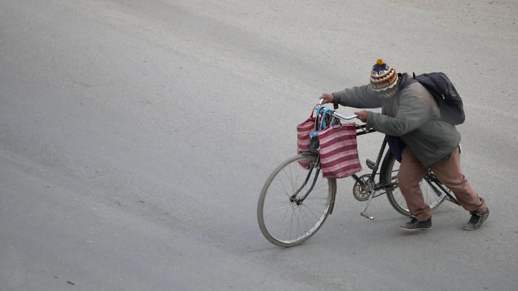 Ciclista arrastrando su bici con bolsas en el manillar, sobre un paisaje monocromo
