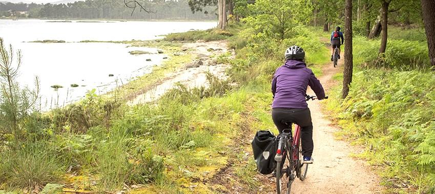 Chica viajando en bici por un sendero ribereño