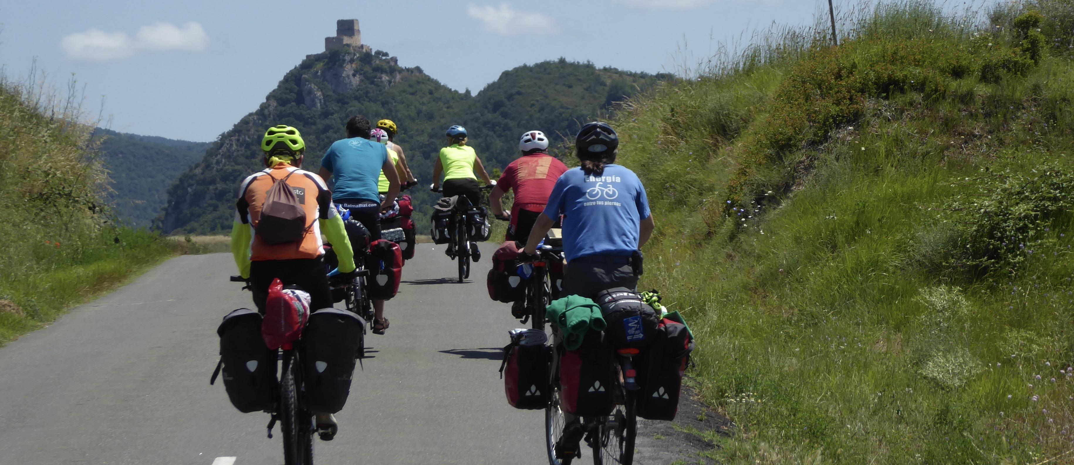 grupo de ciclistas en carretera. Día soleado. Castillo al fondo