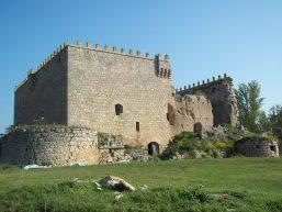 Torre del Castillo de hornaza al fondo sobre pradera verde