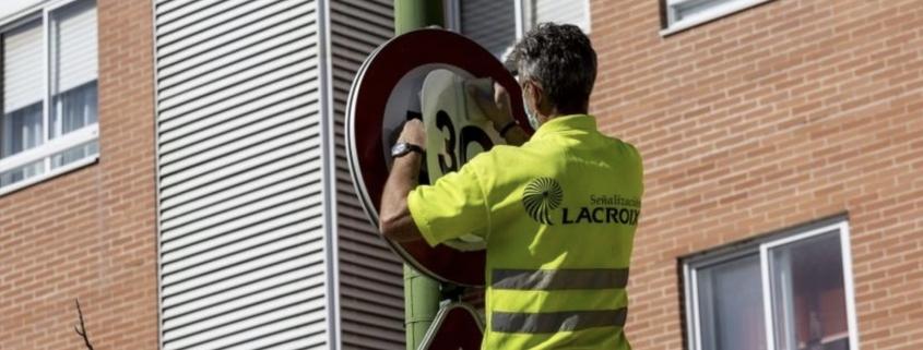 Operario municipal cambiando la señalización del límite de velocidad en la ciudad, de 50 a 30 km/h