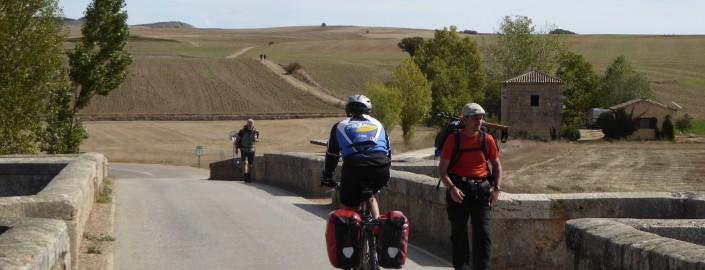 Ciclista y peregrinos en Camino de Santiago.